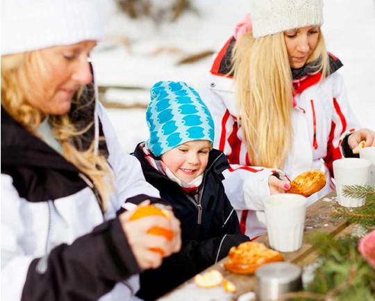 Barn och vuxna äter mellanmål i skidbacken i Väsjön Sollentuna